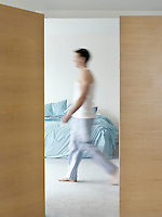 Man walking in bedroom side view (blurred motion)
