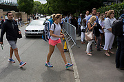 A lady tennis player crosses the road near a queue of spectators during the Wimbledon tennis championships, on 3rd July 2017, in Wimbledon, London, England.