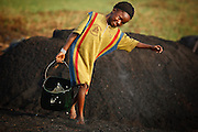A girl carries a bucket of water at a wood charcoal production site on the outskirts of San Pedro, Bas-Sassandra region, Côte d'Ivoire on Sunday March 4, 2012. Men, women and children - who don't go to school - work here seven days a week.