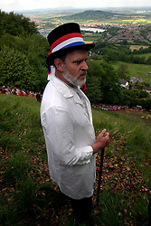 UK ENGLAND COOPERS HILL 31MAY04 - Master of Ceremonies Rob Seex, who has held his function since 1990, gives contestants a somble look before they throw themselves off the top of a steep 200-metre slope in pursuit of a 7-pound Cloucester Cheese. The cheese rolling is one of the oldest customs to have survived some saying, for hundreds of years, even pre-Roman times. The ceremony is reported to.have taken place originally at midsummer and to have been moved to Whitsun in early Saxon times. Some say it is a relic of an old heathen festival to celebrate the return of spring and.others say, when held in midsummer, it represented the waning of the sun as summer reached its height, but no one knows for sure....jre/Photo by Jiri Rezac..© Jiri Rezac 2004..Contact: +44 (0) 7050 110 417.Mobile:  +44 (0) 7801 337 683.Office:  +44 (0) 20 8968 9635..Email:   jiri@jirirezac.com.Web:     www.jirirezac.com