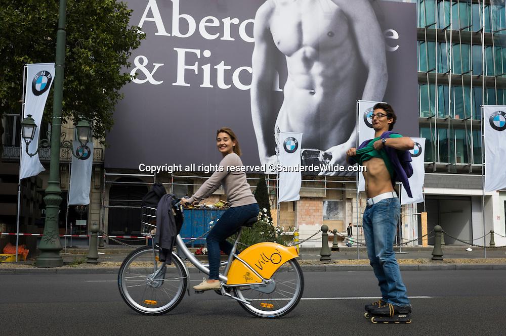 Brussels, 20110918, de autoloze zondag in Brussel. Villofietser en skater langs levensgrote reclame Abercrombie & Fitch, kleine Ring, Louiza.