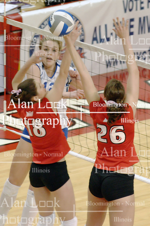 24 November 2006: Kelly Goc slams the ball past the block by Jessie Janik and Kari Staehlin  during a Quarterfinal match between the Illinois State University Redbirds and the Creighton University Bluejays. The Tournament was held at Redbird Arena on the campus of Illinois State University in Normal Illinois.<br />