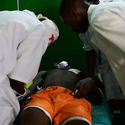 A victim of a grenade attack on a local shop in central Bujumbura, lays on a gurney as medical staff provide medical treatment at Prince Louis Rwagasore Clinic. Eight people were injured in the attack.
