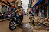 a motor bike passing by a water well installed in the middle of a street, Mysore, India
