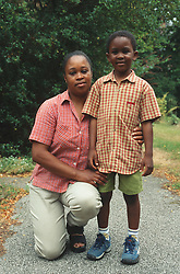 Mother kneeling down on garden path with arm around young son,