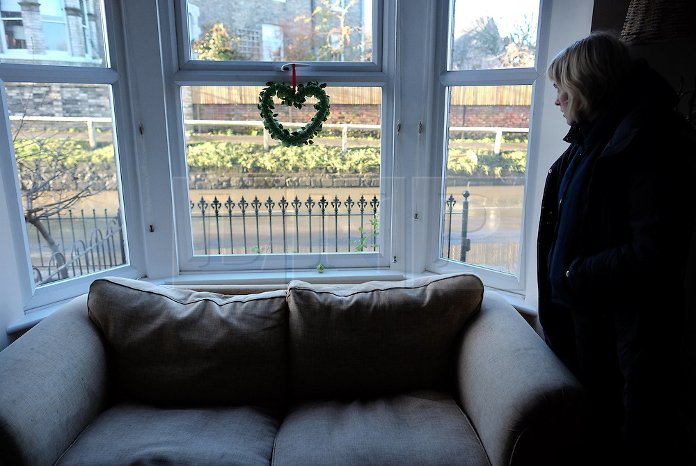 &copy; Licensed to London News Pictures. 29/12/15<br /> York, UK. <br /> <br /> Kate Maughan-Brown looks out of the window of her flooded house as flood water begins to subside on Huntington Road in York. Further rainfall is expected over coming days as Storm Frank approaches the east coast of the country.<br /> <br /> Photo credit : Ian Forsyth/LNP