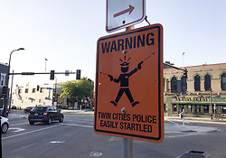 July 23, 2017 - Minneapolis, MN, USA - A fake street sign is mounted on the same pole as legitimate ones at the intersection of Cedar and Riverside Aves. Sunday, July 23, 2017, in Minneapolis. The fatal shooting of an Australian woman by a Minneapolis police officer has sparked the posting of at least two fake street signs warning people of ''easily startled'' officers. The Star Tribune reports the signs were spotted this weekend, one in Minneapolis and one in St. Paul. The official-looking orange metal sign reads: ''WARNING: TWIN CITIES POLICE EASILY STARTLED. (Credit Image: © Erin Adler/TNS via ZUMA Wire)