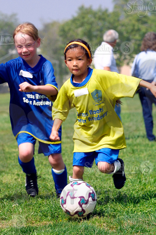 Apr 03, 2002; Irvine, CA, USA; Grass Roots soccer camp for youth kids. Stock photo of two girls running next to eachother one dribbling a ball. <br />