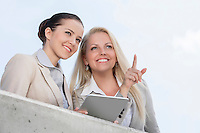 Low angle view of happy businesswoman pointing while standing with coworker on terrace against sky