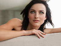 Young woman leaning on couch indoors close-up
