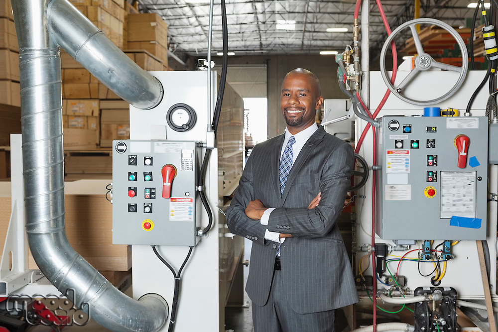 Portrait of African American businessman standing arms crossed with machinery in background