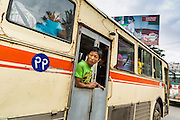 19 JUNE 2013 - YANGON, MYANMAR: A conductor leans out the door of a Yangon bus. Many of buses are imported from Japan, which drives on the left side of the road. Bus owners in Myanmar have had to cut doors into the side of the bus because Myanmar drives on the right. Yangon buses are generally overcrowded and in poor repair but as the economy improves newer, but still used, Japanese and Korean buses are being imported. Hundreds of bus routes criss-cross Yangon, providing the cheapest way of getting around the city. Most fares are less than the equivalent of .20¢ US.   PHOTO BY JACK KURTZ