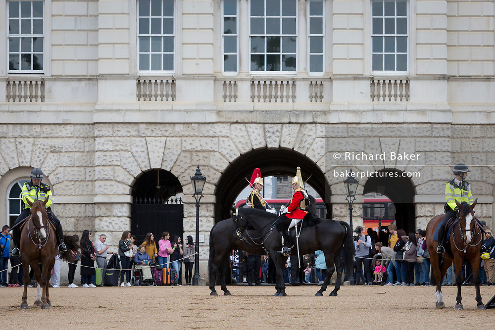 Members of the The Queen's Life Guard (red tunics) and the Blues and Royals (blue tunics) change the guard in front of the public and with a mounted police as security, during the daily ceremonial in Horse Guards Parade, on 11th June 2019, in London, England. Life Guards have stood guard at Horse Guards, the official entrance to St James and Buckingham Palace, since the Restoration of King Charles II in 1660.