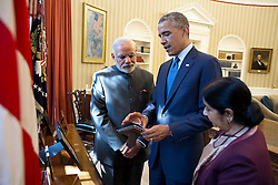 President Barack Obama discusses a photograph with Prime Minister Narendra Modi of India and Minister of External Affairs Sushma Swaraj following a bilateral meeting in the Oval Office, Sept. 30, 2014. (Official White House Photo by Pete Souza) <br /> <br /> This official White House photograph is being made available only for publication by news organizations and/or for personal use printing by the subject(s) of the photograph. The photograph may not be manipulated in any way and may not be used in commercial or political materials, advertisements, emails, products, promotions that in any way suggests approval or endorsement of the President, the First Family, or the White House.