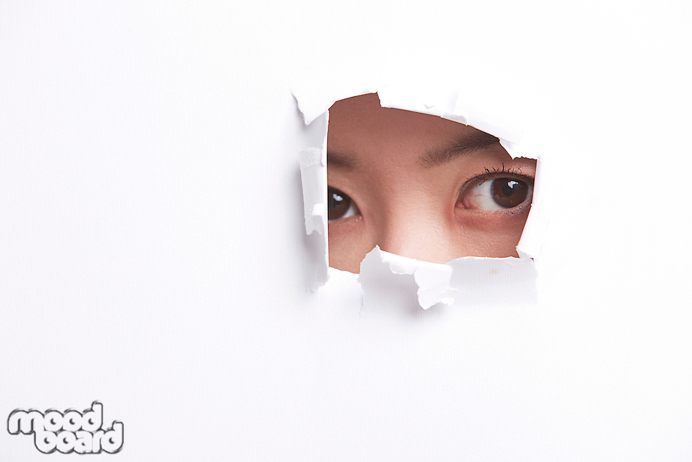 Portrait of young woman peeking through a ripped paper hole