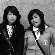 Mirian Torrez Valverde, 17, (left) and Carman Rosa Mamani Singuri, 16, Students. Potosi. Bolivia..Sitting at 4,090M (13,420 Feet) above sea level the small mining community of Potosi, Bolivia is one of the highest cities in the world by elevation and sits ?sky high? in the hills of the land locked nation. Overlooking the city is the infamous mountain, Cerro Rico (rich mountain), a mountain conceived to be made of silver ore. It was the major supplier of silver for the spanish empire and has been mined since 1546, according to records 45,000 tons of pure silver were mined from Cerro Rico between 1556 and 1783, 9000 tons of which went to the Spanish Monarchy. The mountain produced fabulous wealth and became one of the largest and wealthiest cities in Latin America. The Extraordinary riches of Potosi were featured in Maguel de Cervantes famous novel Don Quixote. One theory holds that the mint mark of Potosi, the letters PTSI superimposed on one another is the origin of the dollar sign. Today mainly zinc, lead, tin and small quantities of silver are extracted from the mine by over 100 co-operatives and private mining companies who still mine the mountain in poor working conditions, children are still used in the mines and the lack of protective equipment and constant inhalation of dust means miners have a short life expectancy with many contracting silicosis and dying around 40 years of age. UNESCO designated the historic city a World Heritage site in 1987. Most of Potosí's colonial churches have been restored, and tourism has increased. Potosi, Bolivia. 16th September 2011. Photo Tim Clayton