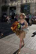 Girl visitor to the RHS Chelsea Flower Show make her way home through Sloane Square after the last day's plant sell-off.