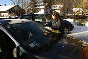 Italy, The Dolomites, Woman scraping ice off her car's windshield on a cold and frosty morning Model Release Available