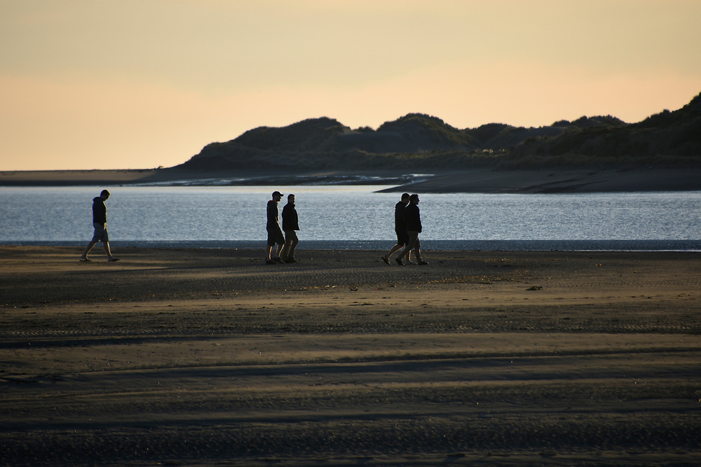 2 men fishing on the sands at sunset in Raglan