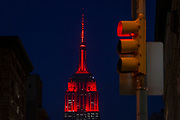 A red signal traffic light in the foreground, while the ESB Empire State Building is lit in red - or maroon - LED light. The color of the ESB was to commemorate Fordham University 175 year anniversary.
