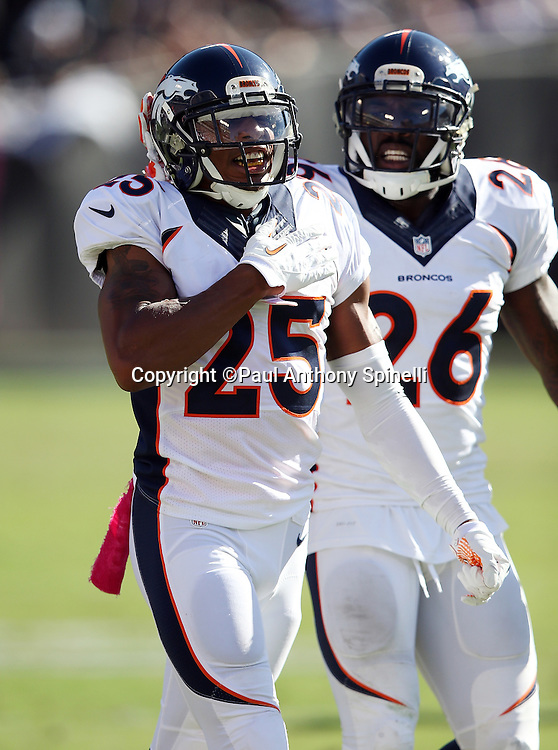 Denver Broncos free safety Darian Stewart (26) looks on as Denver Broncos cornerback Chris Harris Jr. (25) thumps his chest as he celebrates after breaking up a pass play during the 2015 NFL week 5 regular season football game against the Oakland Raiders on Sunday, Oct. 11, 2015 in Oakland, Calif. The Broncos won the game 16-10. (©Paul Anthony Spinelli)