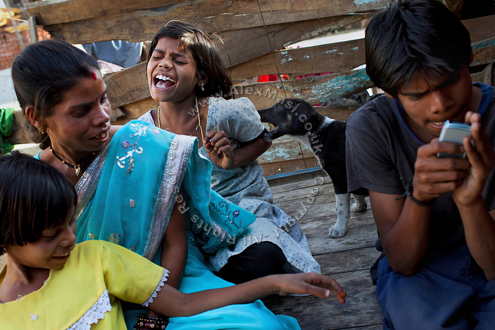 Poonam, 10, (centre) is being bitten on the arm by a stray puppy, taken from the streets of Oriya Basti, one of the water-contaminated colonies in Bhopal, central India, near the abandoned Union Carbide (now DOW Chemical) industrial complex, site of the infamous '1984 Gas Disaster'. Sachin, 18, (right) Poonam's disabled, oldest brother, a boy affected by a lower limbs paralysis, is playing games on a cellphone, while Jyoti, 11, Poonam's sister, and Sangita Jatev, 39, their mother, are sitting in the front yard of their newly built home.