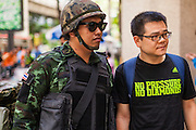 "20 MAY 2104 - BANGKOK, THAILAND:   A Thai soldier poses for snapshots with a Thai tourist at the army checkpoint in Ratchaprasong Intersection after army generals declared martial law. The Thai Army declared martial law throughout Thailand in response to growing political tensions between anti-government protests led by Suthep Thaugsuban and pro-government protests led by the ""Red Shirts"" who support ousted Prime Minister Yingluck Shinawatra. Despite the declaration of martial law, daily life went on in Bangkok in a normal fashion. There were small isolated protests against martial law, which some Thais called a coup, but there was no violence.  PHOTO BY JACK KURTZ"