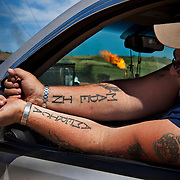 An oil rig supervisor shows off his tattoos at a work site outside of Trenton, North Dakota. The oil boom is redrawing North Dakota's landscape and creating opportunity for thousands of unemployed Americans. However, the economic prosperity has exacerbated problems in housing, infrastructure and traffic...Known for the beauty of its great plains, North Dakota has long been the least populated state in the country. Because of the Bakken oil boom, everyday, mostly men, pour in from across the nation looking for work. The small town of Williston has exploded as a result. Ten years ago Williston, North Dakota was a quiet agricultural town with a population around 12,000. In a decade the population has more than doubled to over 30,000. More than half of Williston's residents now work in oil-related jobs and the city's unemployment rate is at 1 percent, which is the lowest in the U.S...