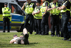 © Licensed to London News Pictures . 02/09/2017 . Keighley , UK . An EDL protester lies on grass and smokes a cigarette at the demonstration , in front of police lines . Far-right street protest movement , the English Defence League ( EDL ) , hold a demonstration in the West Yorkshire town of Keighley , opposed by anti-fascists , including Unite Against Fascism ( UAF ) . The EDL say they are demonstrating against the sexual grooming and abuse of English girls by Muslim men and against terrorism across the UK . Photo credit : Joel Goodman/LNP