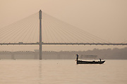 Fisherman using a net from a boat on the river Ganges at Allahabad, Uttar Pradesh, India