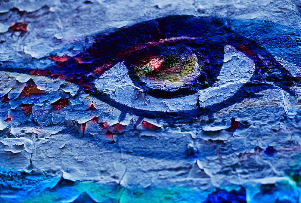 Painted eye on blue wall, peeling paint