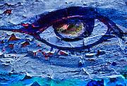 Painted eye on blue wall, peeling paint