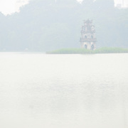 Turtle Tower (Thap Rua), on a small island in the middle of Hoan Kiem Lake in the heart of Hanoi is partially obscured by a thick morning fog. Copyspace at bottom of frame.