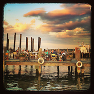 Greenport, NY:  August 9, 2014--- People gather for drinks and dinner and enjoy a good time with a beautiful sunset on a Greenport, Long Island pier on a later summer evening.  © Audrey C. Tiernan
