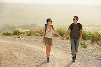Couple of hikers holding hands walking on country road