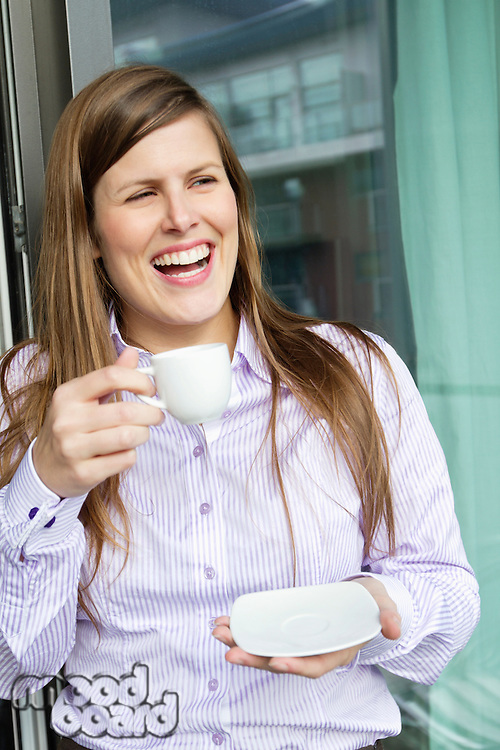 Happy woman holding a cup of coffee and looking away