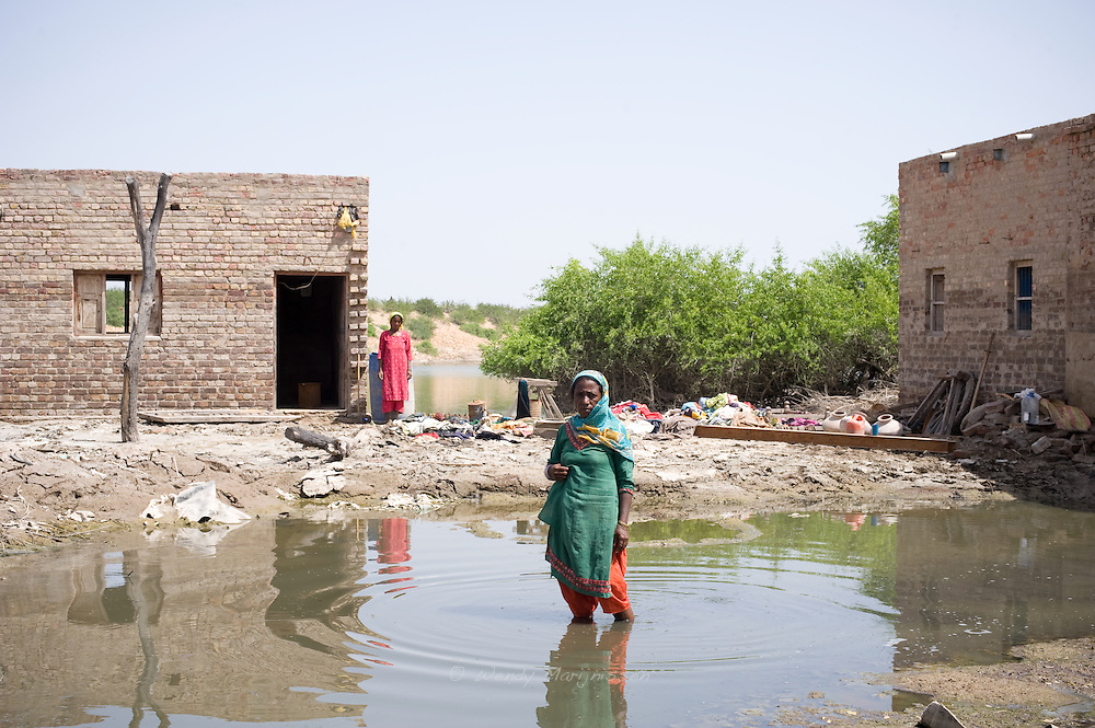 A woman pauzes a moment standing in the water in front of her home and destroyed most of her families belongings. One month after the devastating monsoon rains caused huge floods in Pakistan, new areas are still affected and water still stands among fields and houses.  Jamshoro, Pakistan, 2010