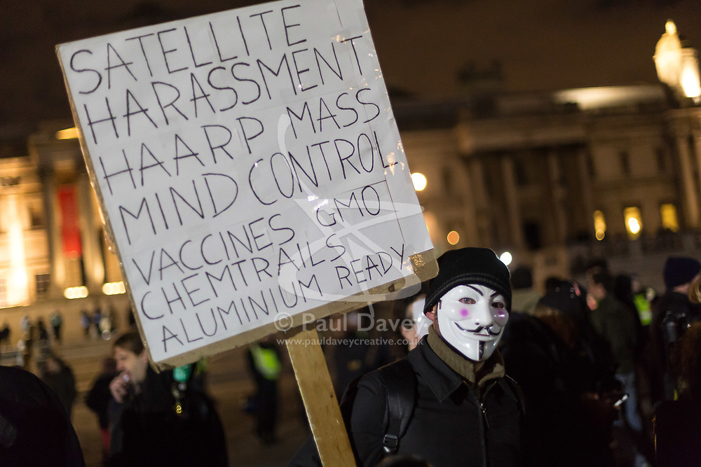 London, November 05 2017. Anti-capitalists gather in Trafalgar Square, London for the annual 'Million Mask March' which happens on November 5th every year, with many of the protesters donning 'V' For Vendetta Guy Fawkes masks. Past marches have turned violent with police horses shot by fireworks and police vehicles burned. PICTURED: A protester's placard shows he's ready and prepared for any number of conspiracy theories.. © Paul Davey