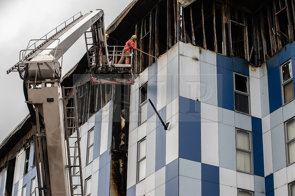 "© Licensed to London News Pictures. 16/11/2019. Bolton, UK. Firefighters remove loose materials amongst cladding from the side of the building at the scene where a fire broke out overnight (15th/16th November 2019) at a block of flats known as "" The Cube "" , in Bolton Town Centre . At least two people are known to have been treated by paramedics at the scene of the six-story block , which is occupied by students of the University of Bolton . Photo credit: Joel Goodman/LNP"
