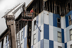 """© Licensed to London News Pictures. 16/11/2019. Bolton, UK. Firefighters remove loose materials amongst cladding from the side of the building at the scene where a fire broke out overnight (15th/16th November 2019) at a block of flats known as """" The Cube """" , in Bolton Town Centre . At least two people are known to have been treated by paramedics at the scene of the six-story block , which is occupied by students of the University of Bolton . Photo credit: Joel Goodman/LNP"""