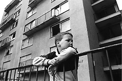 Young boy leaning on railings in front of derelict block of flats; side profile,