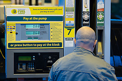 © Licensed to London News Pictures . 03/01/2013 . Oldham , UK . Man filling at petrol pump showing 128.9 pence per litre for unleaded . Supermarket chain Morrisons , in Chadderton Greater Manchester , selling diesel for 135.9 pence per litre and unleaded for 128.9 pence per litre . Photo credit : Joel Goodman/LNP