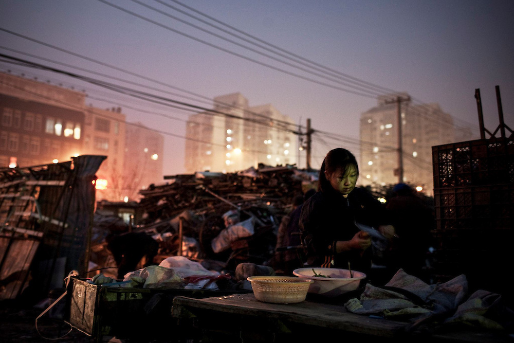 A young woman cooks at the side of a junkyard in Beijing. Around 200 million workers in China are on the 'tramp', erecting the country's shining metropolises as labourers and running the factories as shift workers.<br /> <br /> China's exceptional growth would be inconceivable without this vast army of workers who form the backbone of the Chinese economic boom and are widely regarded as the largest migratory movement in the history of time. And yet theirs is a position on the fringes of society, often living and working in degrading conditions and segregated both socially and legally.<br /> <br /> The 'Migrant Workers' photographic project aims to deal with the situation of these travelling labourers and their families. The main focus of the documentary however will not so much be laid on the conditions of their work, but rather on these people's private lives, their interpersonal relationships, the situation of their families left behind in the country, as well as their overall place in Chinese society.<br /> <br /> Shedding light on the huge diversity of migrant workers in China, photographs will portray examples from all parts of the country and from a wide range of trades, ranging from the classical labourer at one of Shanghai's vast construction sites to the coalminers of the north and the shoe factory seamstresses in the south, all the way to the hostesses at the karaoke clubs in the country's new boomtowns, the chefs and waiters at the large Beijing restaurants and the domestic helpers employed by rich Hong Kong families.