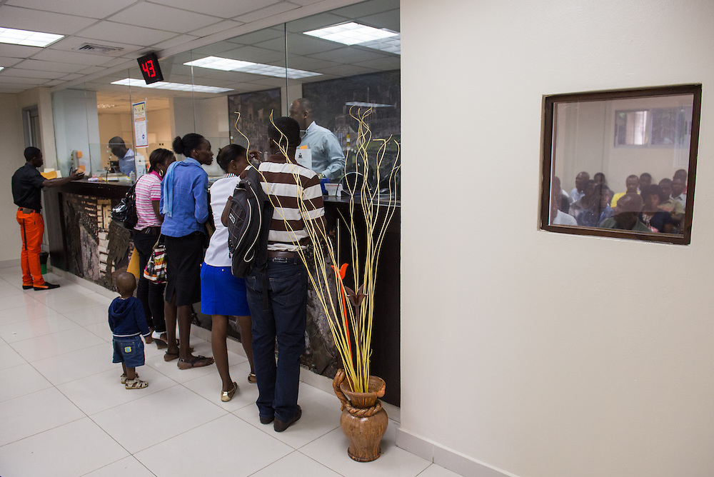 Working for the Spanish nonprofit Justalegria, Jackson Chancy (far left in orange pants) applies for Haitian passports at the Haitian Embassy in Santo Domingo, Jan. 7, 2014. The program helps document Haitian mothers from the bateys so that their Dominican-born children may also be documented, but the process is often thwarted by beauracracy. Jackson would have to make the two hour trip by public bus later in the week when the passports he was told were completed were not, in fact, ready for pick-up that day.