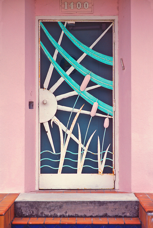 A Tropical Deco screen door on a single family home in the Flamingo Park area of Miami Beach, Florida. The pressed metal design, featuring sunbeams,  tropical vegetarion and ocean waves, probably dates back to the late-1930s or early 1940s. Screen doors like this were typical in South Florida before airconditioning became commonplace. This photograph was made in 1993, but as of 2016, this remarkable vintage door still survives there.