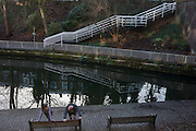 Two joggers stretch stiff muscles, on 2nd January 2017, in Regent's Canal, central London, England.