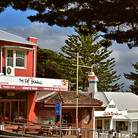 Resort Town of Cowes on Phillip Island, Australia<br /> Almost half of Phillip Island&rsquo;s population of 9,400 people lives in Cowes. During the summer months, this resort town swells with visitors. A cluster of retailers and cafes hug the gentle slope of Thompson Avenue. Tourists are shaded from the sun by an impressive canopy of Australian golden cypress. These trees can reach a height of 65 feet. Hotels and the best restaurants face the shore along The Esplanade. The most popular watering hole is at the North Pier Hotel.