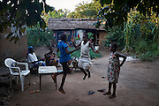 "Esperance Mulwefakadi (white dress) plays with friends while her family prepare dinner at the family home in Kikwit, Bandundu Province, Democratic Republic of Congo on November 14, 2014. Esperance received a scholarship through the program 'VAS-Y Fille' and has been able to continue the last two years of school. From a disadvantaged family, her mother has been sick and bed ridden for many years and her father and extended family whom she lives with scrape by collecting manyok roots which they dry and sell to make a meagre living. ""I would like to continue my studies into high school if my family has the means to support me and I dream of one day becoming a nurse."" The Bana Kimono primary school has 394 students with 40 in total female students receiving a scholarship from years 5 & 6. CRS with partner Caritas and organisations International Rescue Committee and Save the Children are engaged in a education initiative focusing on assisting female students from financially disadvantaged families continuing studies in the final two years of primary school. The program 'VAS-Y Fille' or 'Go Girl!' supplies scholarships to help pay the school fees and books for students from disadvantaged families."
