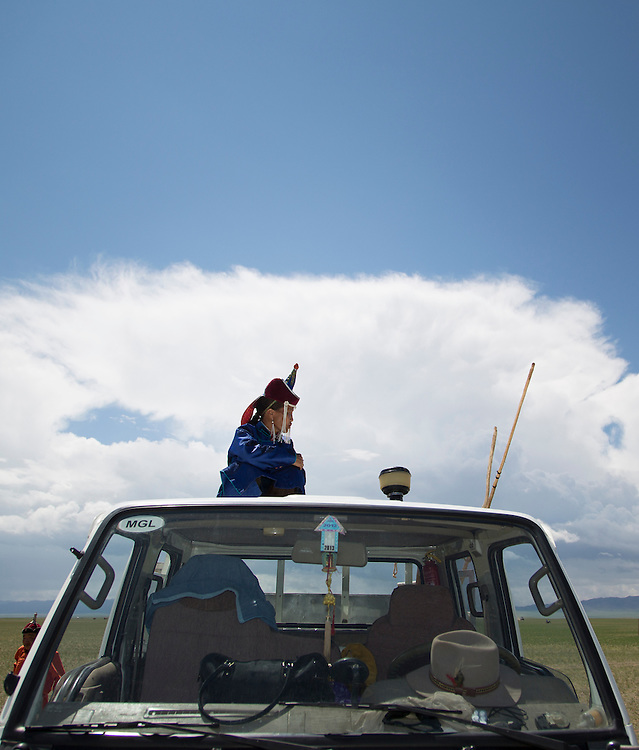 A Mongolian woman sits on top of her truck watching the wrestling competition of Naadam Festival at the Three Camel Lodge in the Gobi Desert of Mongolia on July 31, 2012. © 2012 Tom Turner Photography