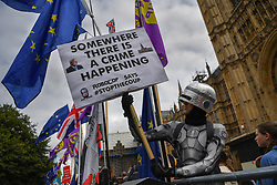© Licensed to London News Pictures. 03/09/2019. London, UK. Charlie Rome, 35 from Charlton dressed as Robocop holds a banner reading 'Somewhere there is a crime Happening'. Protesters assemble opposite the Palace of Westminster at the beginning a long day as MPs meet to block the suspension of Parliament.  Photo credit: Guilhem Baker/LNP